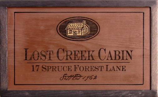 Pine wooden sign featuring a log cabin, cabin signs